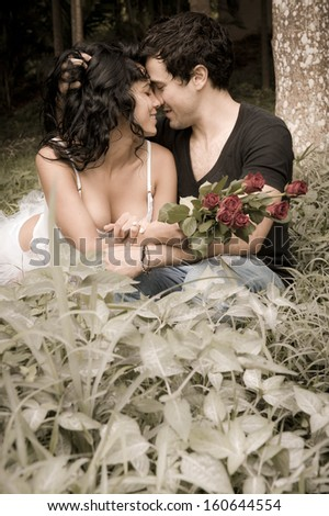 Young beautiful caucasian couple sitting in forest with bunch of red roses sharing an intimate moment - stock photo
