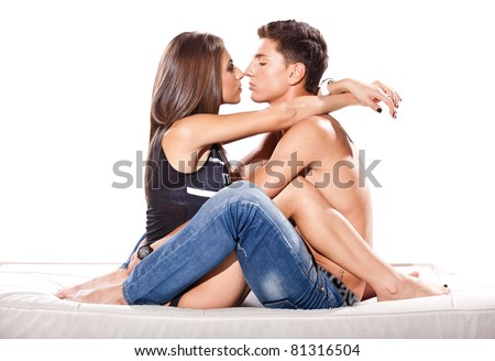 Young beautiful caucasian couple sitting on sofa and hugging - stock photo