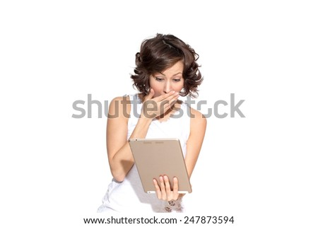 Young beautiful caucasian female brunette model in white t-shirt posing with expressive emotion, hand near mouth, exited, shocked, surprised when looking at tablet pc isolated on white - stock photo