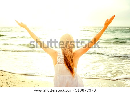 young beautiful caucasian female enjoying the sun on beach during sunrise or sunset