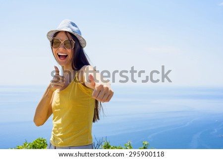 young beautiful caucasian female on a cliff above the sea - stock photo