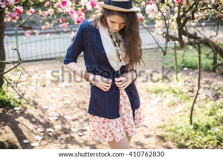Young beautiful caucasian girl in a blossoming spring magnolia garden. The girl in the garden morning. Boho style. Portrait. The girl in the hat, necklace and earrings. Girl corrects cardigan. - stock photo