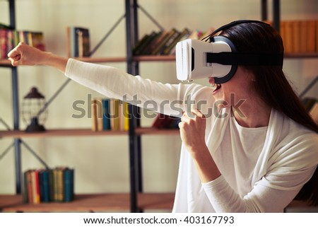 Young beautiful Caucasian girl punch someone playing with VR headset glasses