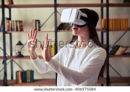Young beautiful Caucasian girl with long hair wearing VR glasses - stock photo