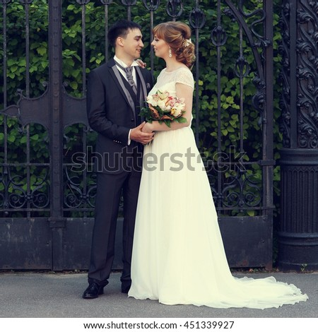 Young beautiful caucasian just married couple standing near cast iron lattice tracery on a summer day at sunset. Beautiful bride in white dress and groom in luxury costume