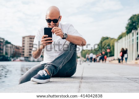 Young beautiful caucasian man, sitting on the riverbank, taking pictures with smart phone hand hold, smiling - technology, social network, happiness concept  - stock photo