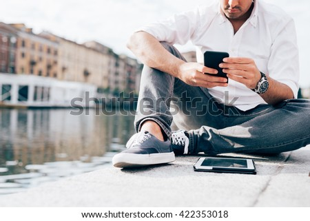 Young beautiful caucasian man, sitting on the riverbank, using smart phone hand hold - technology, social network, happiness concept - stock photo