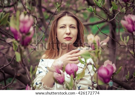 Young beautiful caucasian woman in blooming spring garden of magnolias . The girl in the garden on a cloudy day . High-fashion. Close-up portrait - stock photo
