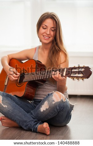 Young beautiful caucasian woman in casual playing guitar - stock photo
