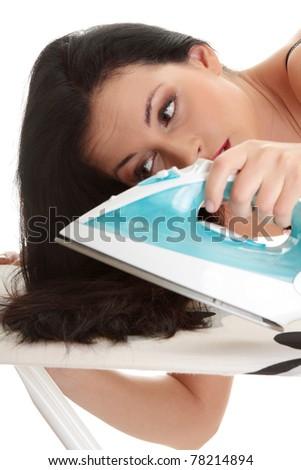 Young beautiful caucasian woman ironing her hairs - stock photo