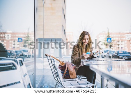 Young beautiful caucasian woman sitting on a bar having a cup of coffee, looking downward and tapping the screen of a smart phone hand hold - break, relax, technology concept