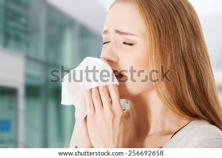 Young beautiful caucasian woman sneezing - stock photo