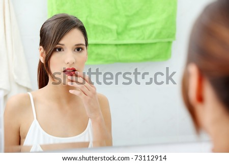 Young beautiful caucasian woman stands about a mirror in a bathroom - stock photo