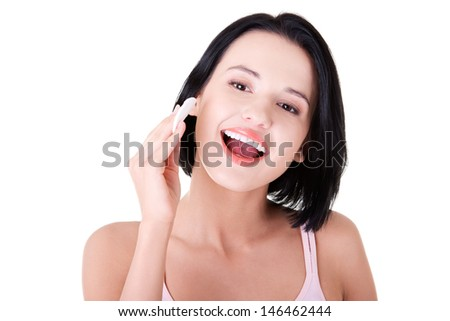 Young beautiful caucasian woman using a cotton pad to remove her make-up. Isolated on white  - stock photo