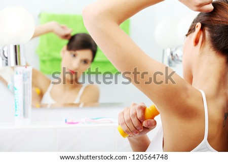 Young beautiful caucasian woman using deodorant at her bathroom - stock photo