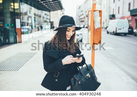 Young beautiful caucasian woman waiting at the bus stop outdoor in the city, looking down and tapping the screen of a smart phone handhold - commuter, technology, happiness concept - stock photo