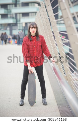 Young beautiful caucasian woman walking through the streets of the city with a skateboard posing and looking in camera - youth, freshness, carefree concept - stock photo