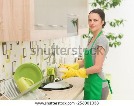 young beautiful caucasian woman washing dishes - stock photo