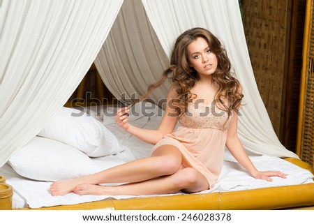 Young beautiful caucasian woman wearing white lingerie lying on the bed in bedroom - stock photo