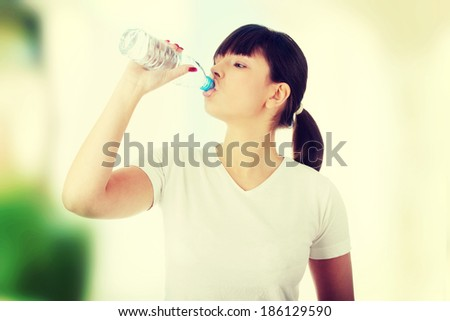 Young beautiful caucasian woman with bottle of mineral water - stock photo