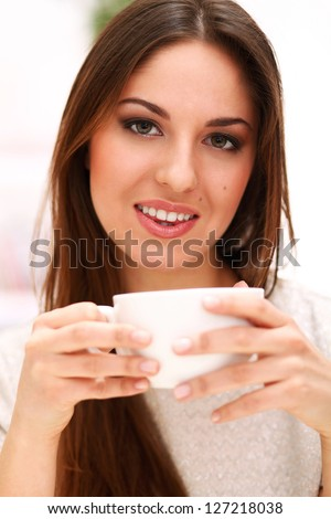 Young beautiful caucasian woman with cup at home