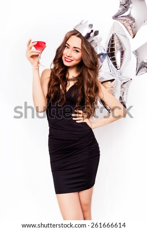 Young beautiful  celebrating  woman in  black dress   smile and posing with cocktail in hand and purity balloons . Beautiful model portrait isolated over studio background. - stock photo