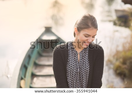 Young beautiful charming woman at the old fishing boat smiling.Honest reaction on a  male complimenting.Compliment concept.Paying a compliment beautiful woman - stock photo