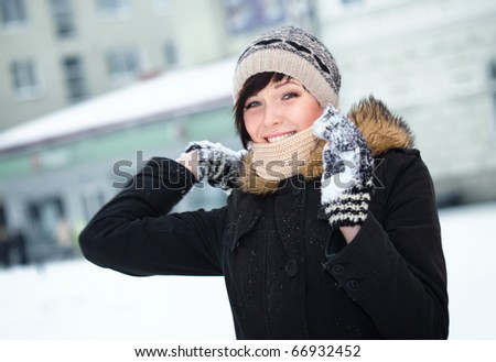 Young beautiful cheerful girl is throwing snowball - stock photo