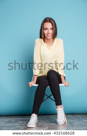 Young beautiful cheerful girl sitting on chair isolated on the blue background