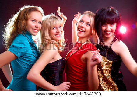 Young beautiful cheerful girls dancing at  party - stock photo