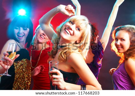 Young beautiful cheerful girls dancing at  party