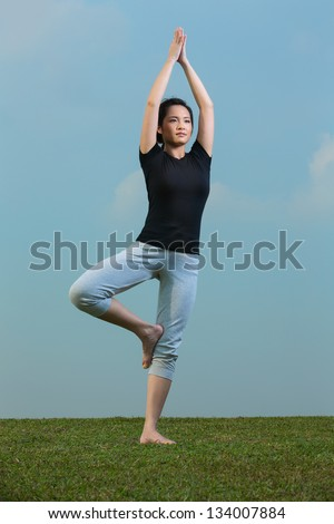 Young beautiful Chinese woman standing meditating in a yoga pose on grass. Asian Woman in black t-shirt Performing yoga. - stock photo