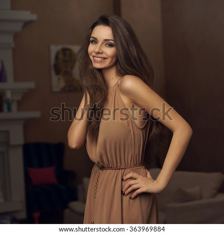 Young beautiful classy girl standing and posing in brown long evening dress in comfortable home interior - stock photo