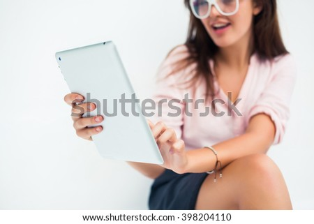 young beautiful clever girl with long hair in glasses posing sitting in a cafe with tablet in hand, lovely woman, works, responds to messages in facebook, posting photos to instagram, outdoor portrait - stock photo
