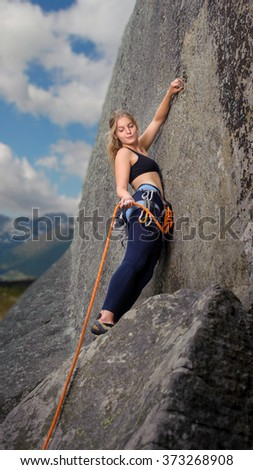 Young beautiful climber climbing with rope and carbines on a big boulder, holding the rope. Mountains and blue sky on the background. Summer time.