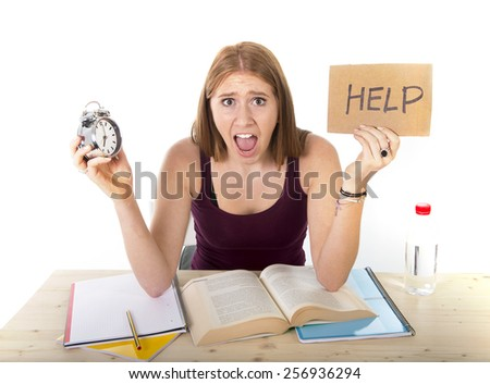 young beautiful college student girl studying for university exam in stress asking for help holding alarm clock test deadline time pressure sitting on desk in education concept - stock photo