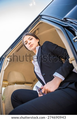 Young beautiful confident businesswoman in suit sitting in her luxurious car.