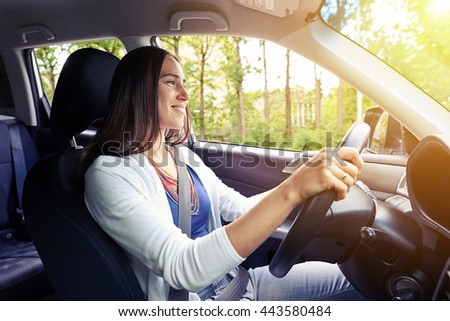 Young beautiful confident smiling woman is driving on a sunny day with her seat belt fastened - stock photo