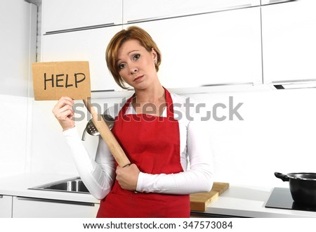 young beautiful cook woman in angry upset and frustrated face expression wearing red apron asking for help holding rolling pin at home kitchen in domestic stress and lifestyle concept
