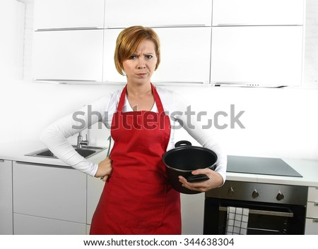 young beautiful cook woman in angry upset and frustrated face expression wearing red apron holding cooking pot and rolling pin at home kitchen in domestic stress and lifestyle concept - stock photo