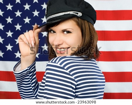 young beautiful coquettish sailor standing near the American flag and smiling