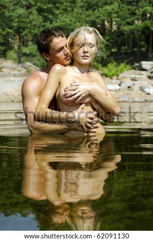 Young beautiful couple are kissing and holding in the water - stock photo