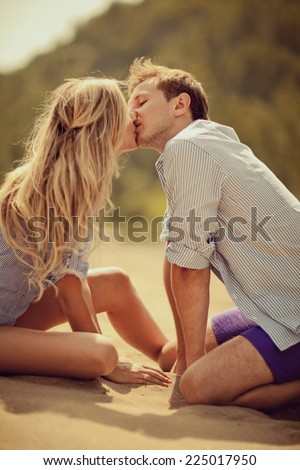 Young beautiful couple are kissing on the beach - stock photo