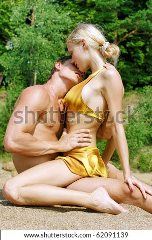 Young beautiful couple are kissing on the beach