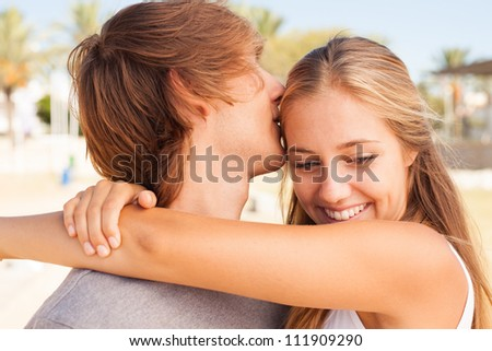 Young beautiful couple closeup portrait at the beach on sunny day