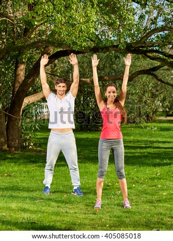 Young beautiful couple doing exercises outdoors in the park. Full-length. - stock photo