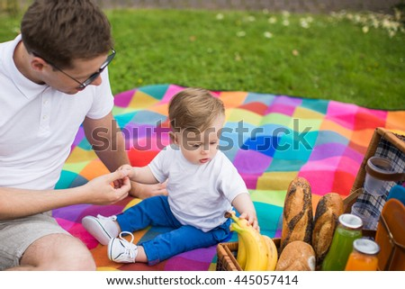 Young beautiful couple dressed casual lying on the lawn in summer park.