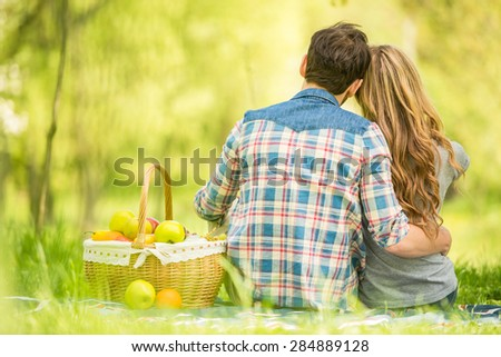 Young beautiful couple dressed casual on romantic picnic in summer park. - stock photo