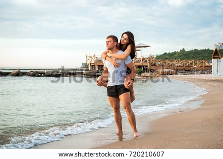 Young beautiful couple embracing, having sun on beach