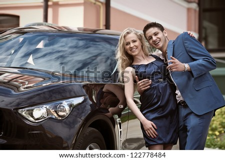 Young beautiful couple end car - stock photo